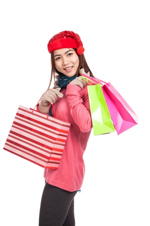 Asian girl with red christmas hat with shopping bags  isolated on white background photo