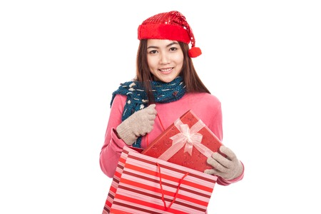Asian girl with christmas hat pull gift box from shopping bag  isolated on white background photo