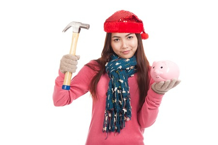 Asian girl with red christmas hat ,hammer and piggy bank  isolated on white background photo