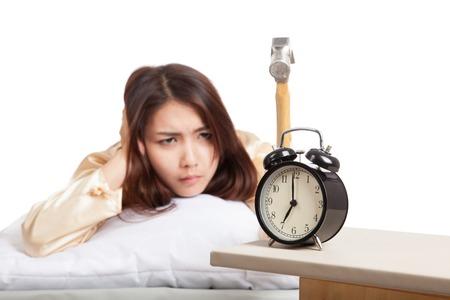 Sleepy Asian girl wake up hit alarm clock with hammer  isolated on white background Stock Photo