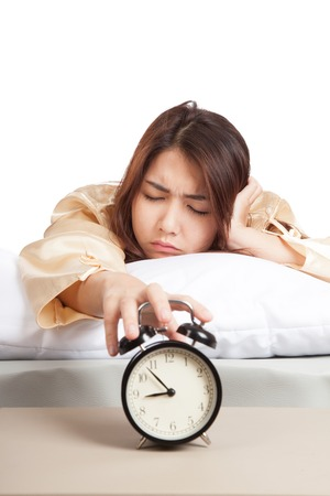 Sleepy Asian girl with alarm clock  isolated on white background Foto de archivo