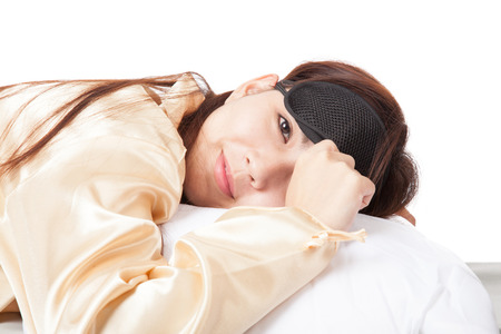 Happy Asian girl with eye mask wake up and smile  isolated on white background photo