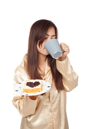 Asian woman in pajamas with coffee and heart shape jam on bread  isolated on white background photo