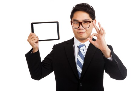 Asian businessman show OK with  tablet pc  isolated on white background photo
