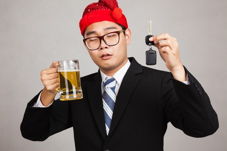 Asian businessman with party hat ,drink beer,get drunk, hold car key on gray background photo