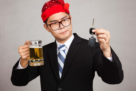 Asian businessman with party hat decide drink or drive with beer and car key on gray background photo