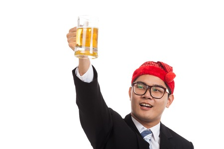 Asian businessman with red  christmas hat cheers with mug of beer  isolated on white background photo