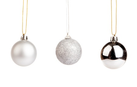 Three of silver color christmas tree baubles isolated on white background Foto de archivo