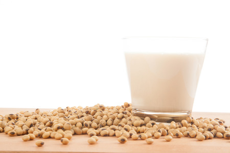 Soy milk in glass with soybeans on wood table