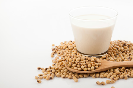 Soy milk in glass with soybeans and wooden spoon on white background