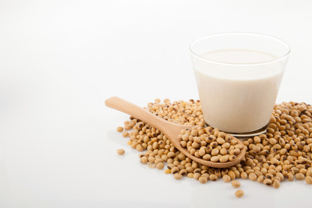 Soy milk in glass with soybeans and wooden spoon on white background Banco de Imagens - 34394985