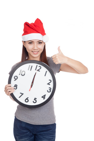 Asian girl with red santa hat and clock show thumbs up  isolated on white background Stock Photo - 34515437
