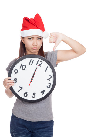 Asian girl with red santa hat and clock show thumbs down  isolated on white background photo