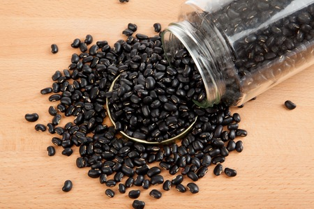 black gram: Black beans in a jar on wood table with lid off Stock Photo