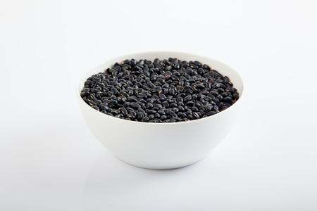 black gram: Black beans in a white bowl  on white background Stock Photo