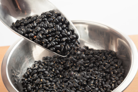black gram: Black beans in bowl with transfer scoop on wood table Stock Photo