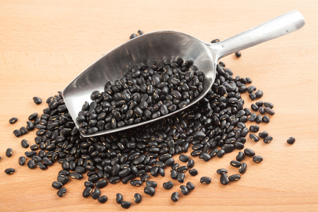 black gram: Black beans with transfer scoop on wood table