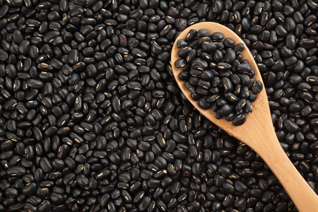 black gram: Black beans with wooden spoon on black beans  background