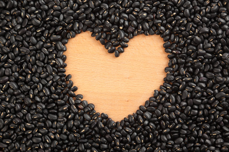 black gram: Black beans with wooden  heart shape space at center Stock Photo