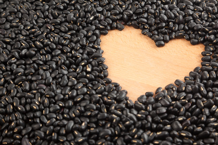 black gram: Black beans with wooden heart shape space Stock Photo