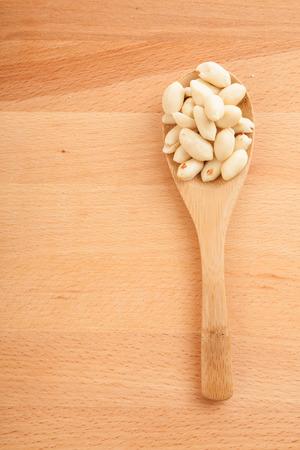 madera: Cacahuetes pelados con cuchara de madera sobre fondo de madera