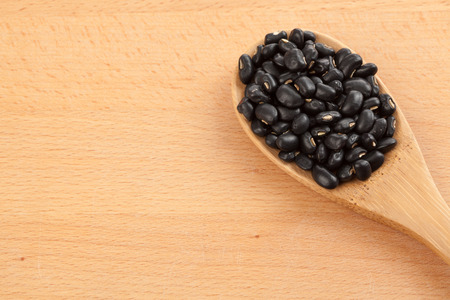 black gram: Black beans with wooden spoon on wood background