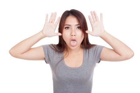 sticking out tongue: Mujer asi�tica joven divertido sacar la lengua aislada en el fondo blanco