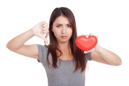 corazon roto: Mujer asi�tica joven Pulgares abajo con el coraz�n rojo aislado en fondo blanco