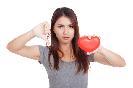 broken relationship: Young Asian woman thumbs down with red heart  isolated on white background Stock Photo