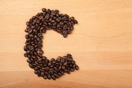 letter c: Roasted coffee beans in letter C shape  on wooden background