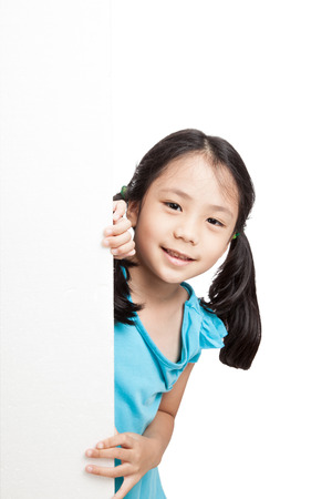 Little asian girl peeking behind a white board  isolated on white background Reklamní fotografie