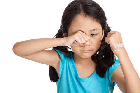 ouch: Little asian girl cry with bandage on her hand  isolated on white background Stock Photo
