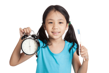 human teeth: Little asian girl smile with a clock and toothbrush  isolated on white background