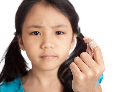 ouch: Little asian girl show finger with bandage  isolated on white background