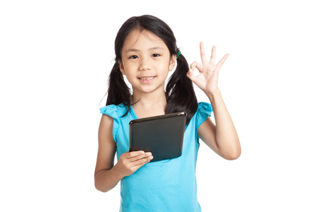 Little asian girl show OK with tablet pc  isolated on white background