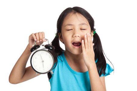 Little asian girl sleepy with a clock  isolated on white background