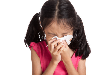 flu: Little asian girl sneeze with napkin paper  isolated on white background