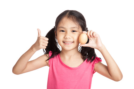 Little asian girl thumbs up with an egg in hand  isolated on white background