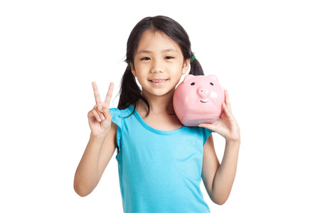 show of hands: Little asian girl show victory sign with piggy bank  isolated on white background