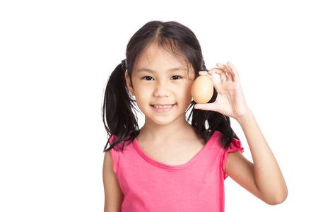 huevo blanco: Ni�a asi�tica sonrisa con un huevo en la mano aisladas sobre fondo blanco Foto de archivo