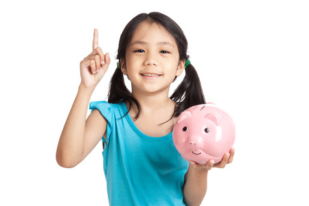Little asian girl point up with piggy bank  isolated on white background