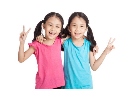 identical: Happy Asian twins girls  smile show victory sign  isolated on white background Stock Photo