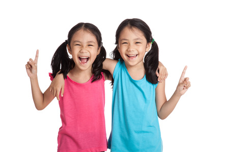 Happy Asian twins girls  smile point up  isolated on white background