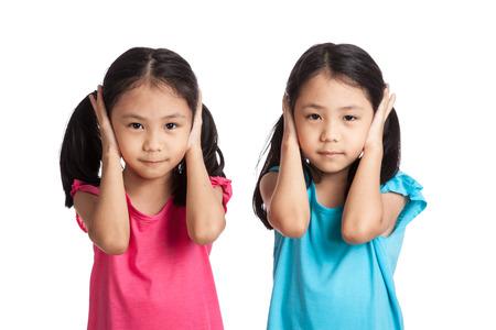 oido: Gemelos chicas asiáticas se tapan los oídos aislados en el fondo blanco