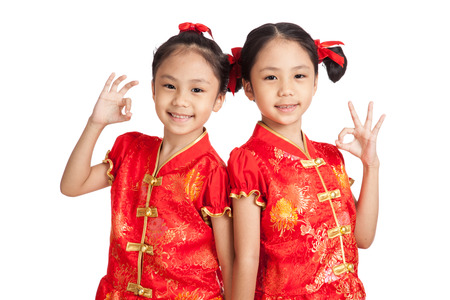 children celebration: Asian twins girls in  chinese cheongsam dress show OK sign  isolated on white background