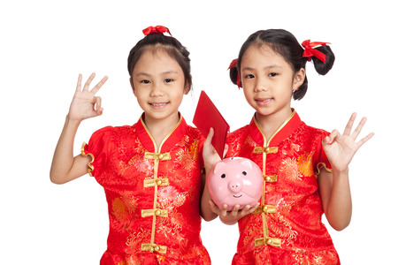 Asian twins girls in  chinese cheongsam dress with coin bank and red envelopes  isolated on white background Stock Photo