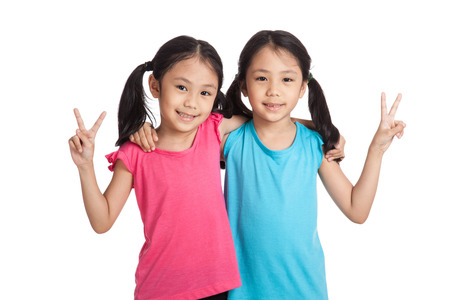 victory sign: Happy Asian twins girls  smile show victory sign  isolated on white background Stock Photo
