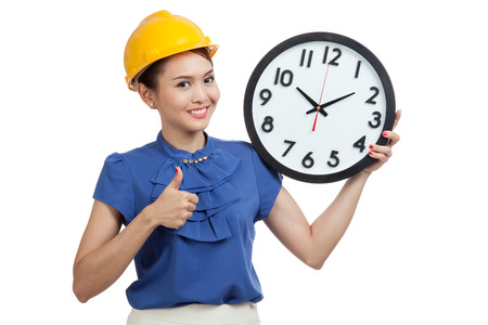 femme pouce leve: Asian engineer woman thumbs up with a clock  isolated on white background