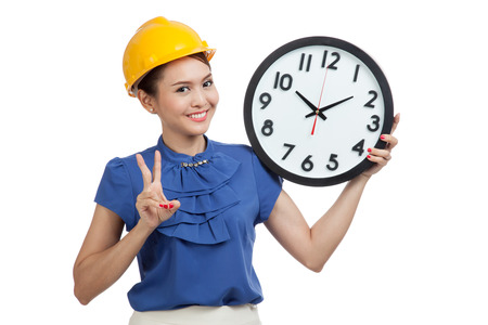 clock: Asian engineer woman show victory sign with a clock  isolated on white background Stock Photo