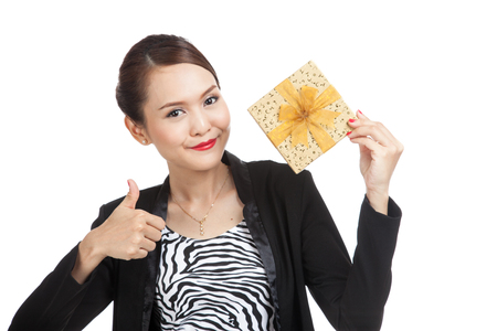 femme pouce leve: Young Asian business woman thumbs up with a golden gift box  isolated on white background